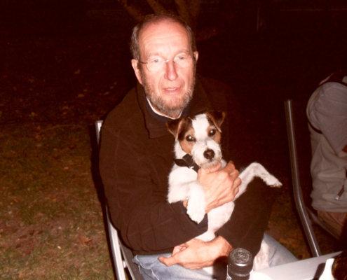 zeigt einen Mann mit Hund im Arm