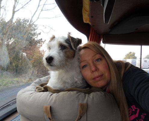 zeigt eine junge Frau und einen Terrier im Wohnmobil