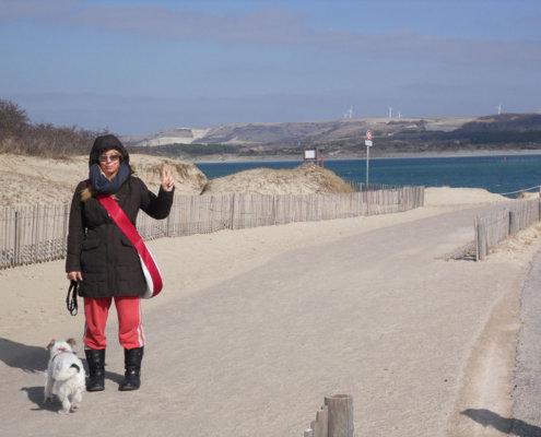 zeigt eine junge Frau und einen Hund dick angezogen am Strand