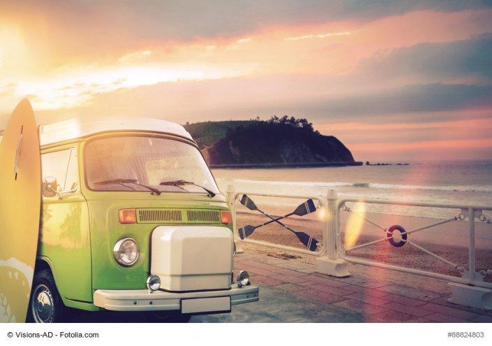Kleinbus mit Surfbrett am Meer