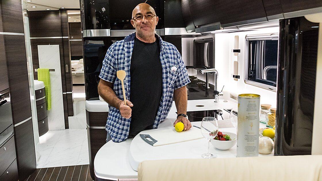 zeigt einen Mann in der Küche eines Wohnmobils