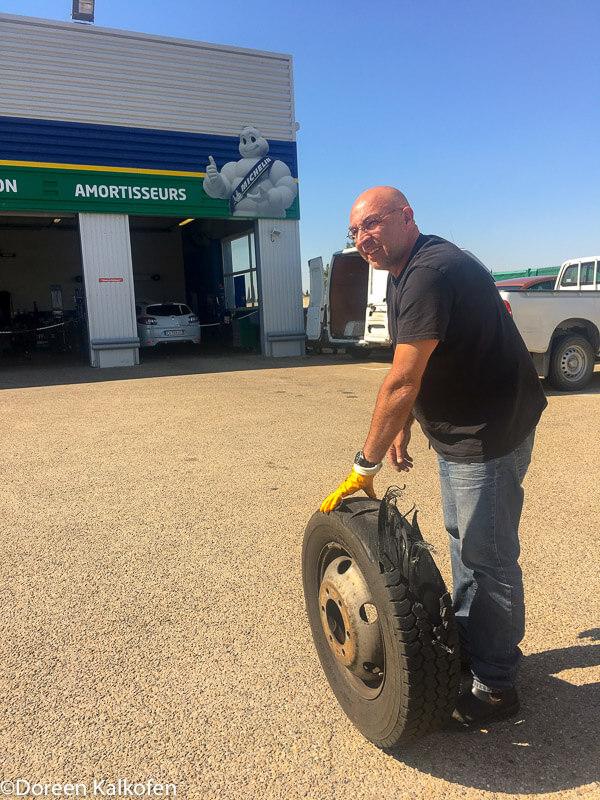 zeigt einen Mann der einen kaputten Reifen in eine Werkstatt rollt