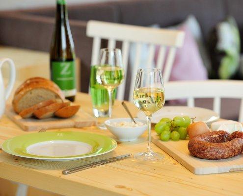 zeigt einen gedeckten Tisch mit Wein, Brot, Käse & Wurst