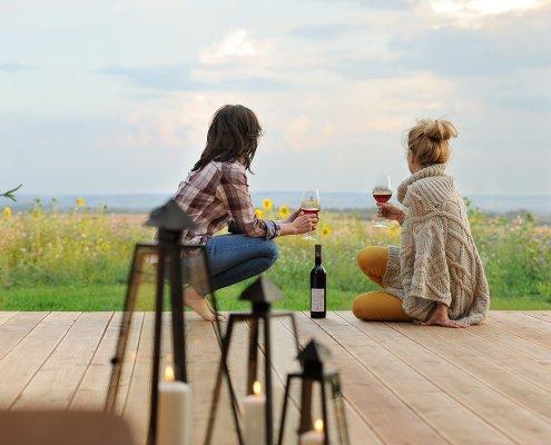 zeigt 2 Frauen auf einer Terrasse mit Blick in die Natur
