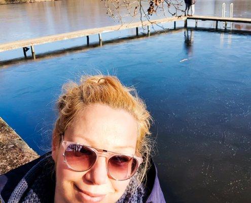 zeigt eine Frau mit Sonnenbrille am See