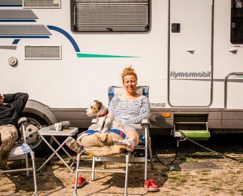 zeigt ein Pärchen vor einem Wohnmobil auf Campingstühlen