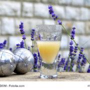 zeigt ein Glas Pastis und Lavendel