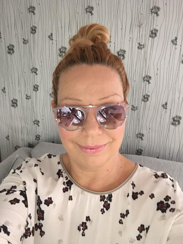 zeigt eine blonde Frau mit Sonnenbrille