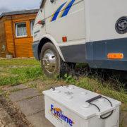 zeigt eine Batterie neben einem Wohnmobil