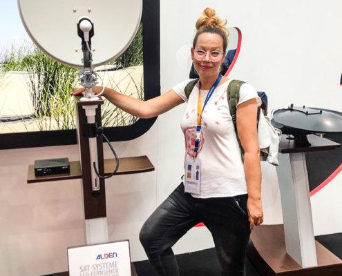 zeigt eine Frau mit ihrer Lieblings Sat -Antenne von Alden