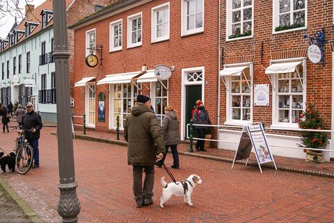 zeigt eine friesische Einkaufsstrasse mit Mann und Hund