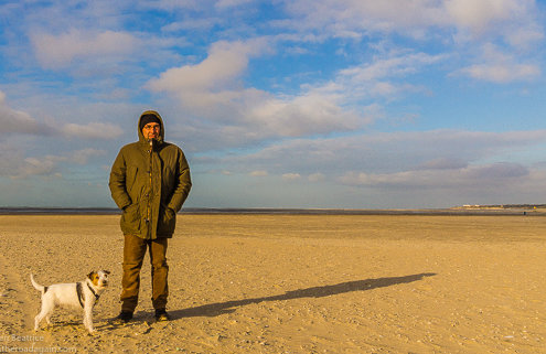 zeigt einen Mann und einen Hund am strand