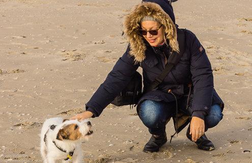 zeigt eine Frau und einen Hund am Strand