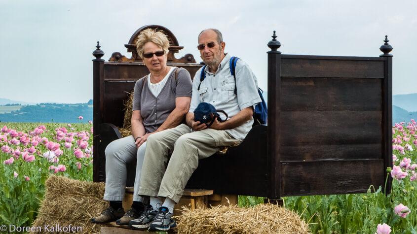 zeigt zwei Menschen auf übergroßem Bett im Mohnfeld