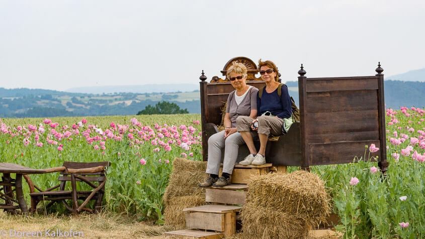 Zeigt 2 Frauen auf einem übergroßen Bett im Mohnfeld