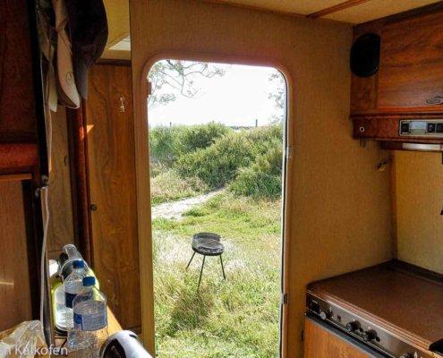 Ausblick aus Wohnmobil auf Grill und Grünfläche
