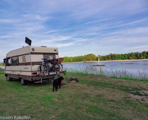 Erste Reise Wohnmobil zeigt ein Wohnmobil am Ufer eines Flusses